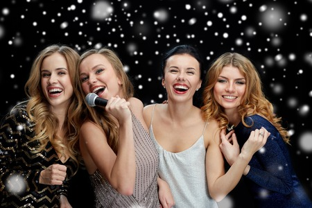 holidays, friends, bachelorette party, nightlife and people concept - three women in evening dresses with microphone singing karaoke over black background