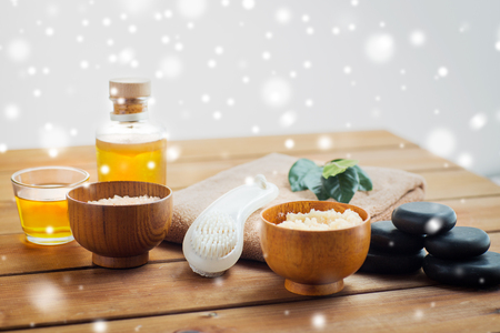 lastone therapy: beauty, spa, bodycare, natural cosmetics and massage concept - body scrub with brush and massage oil on wooden table over snow