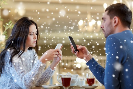 people, communication and dating concept - couple with smartphones drinking tea at cafe or restaurant Stock Photo