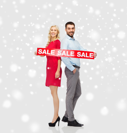 people, christmas, shopping, winter and holidays concept - happy couple with red sale sign over snow background