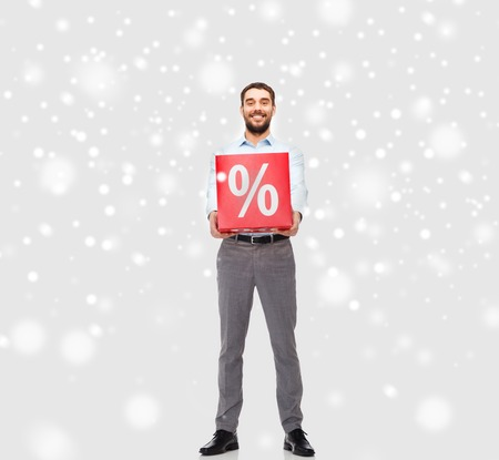 percentage sign: people, sale, shopping, christmas and winter holidays concept - smiling man holding red percentage sign over snow background