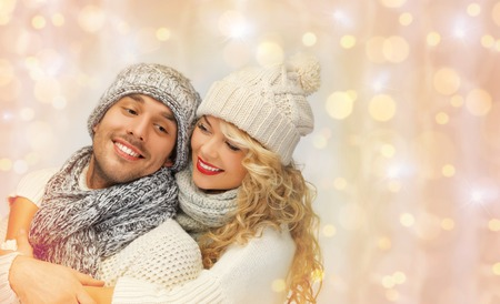 happy christmas: people, christmas, holidays and new year concept - happy family couple in winter clothes hugging over holidays lights background