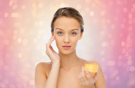 cosmetics background: beauty, people, cosmetics, skincare and cosmetics concept - young woman applying cream to her face over rose quartz and serenity lights background