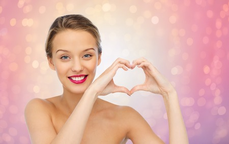 heart in hand: beauty, people, love, valentines day and make up concept - smiling young woman with pink lipstick on lips showing heart shape hand sign over rose quartz and serenity lights background