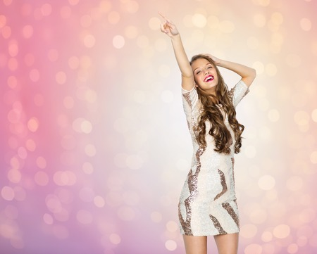 sequins: people, style, holidays and fashion concept - happy young woman or teen girl in fancy dress with sequins and long wavy hair dancing at party over rose quartz and serenity lights background