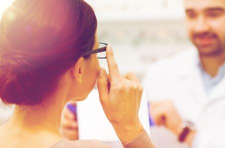 gezondheidszorg, mensen, gezichtsvermogen en visie concept - close-up van opticien en vrouw kiezen bril op optica winkel Stockfoto