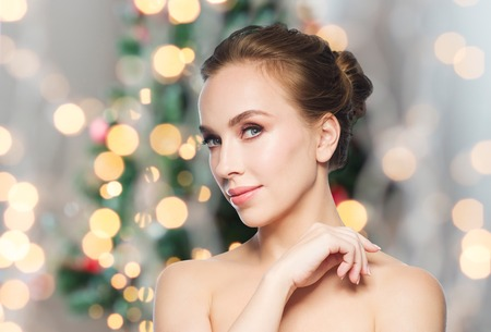young tree: beauty, people and winter holidays concept - beautiful young woman face over christmas tree lights background