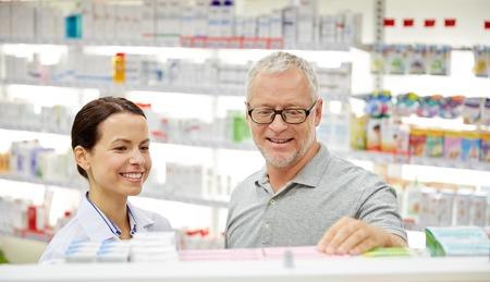 pharmaceutics: medicine, pharmaceutics, health care and people concept - happy pharmacist talking to senior man customer at drugstore