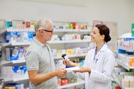 pharmaceutics: medicine, pharmaceutics, health care and people concept - happy pharmacist giving drug to senior man customer and taking prescription at drugstore