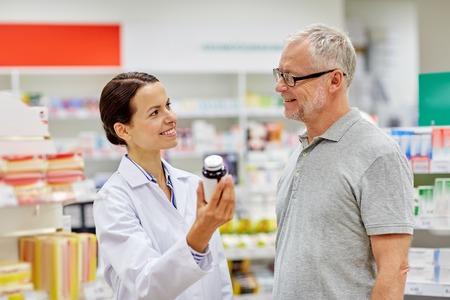 pharmaceutics: medicine, pharmaceutics, health care and people concept - happy pharmacist showing drug to senior man customer at drugstore