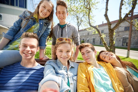 best schools: education, high school and people concept - group of happy teenage students or friends taking selfie