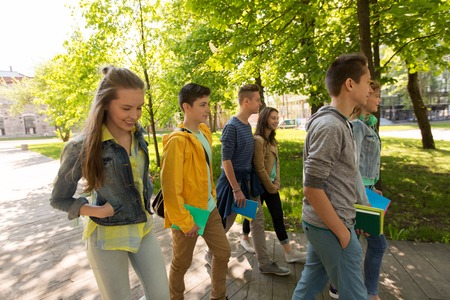 school teens: education, high school, learning and people concept - group of happy teenage students walking outdoors