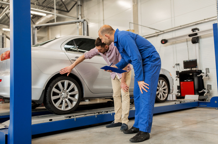 自動サービス、修理、保守および人々 コンセプト - クリップボードと男やカーショップで所有者とメカニック