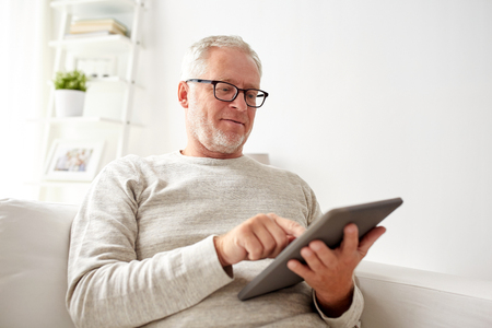 viewing: technology, people and lifestyle concept - senior man with tablet pc computer at home Stock Photo
