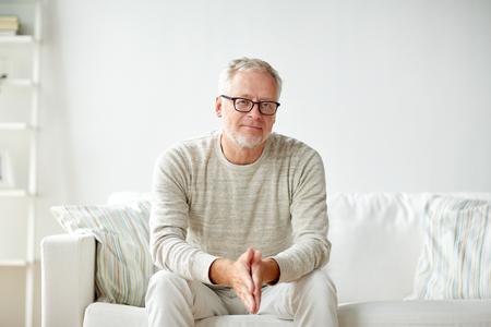 노인, 안락 및 사람들이 개념 - 집에서 소파에 앉아 안경에 웃는 수석 남자