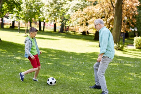 family, generation, game, sport and people concept - happy grandfather and grandson playing football at summer park Imagens