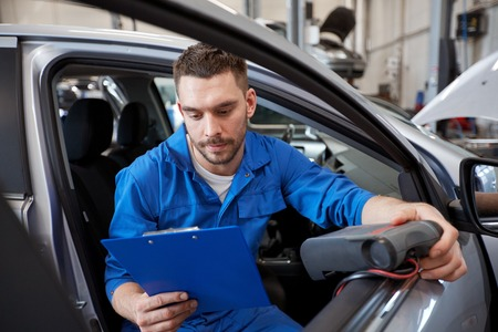 서비스, 복구, 유지 보수 및 사람들이 개념 - 자동차 진단 스캐너 및 클립 보드 검사 정비공 자동차 시스템에서 워크샵