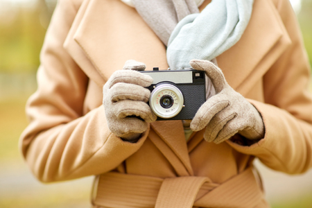 photo shooting: season, photography and people concept - close up of young woman taking picture with vintage camera in autumn park