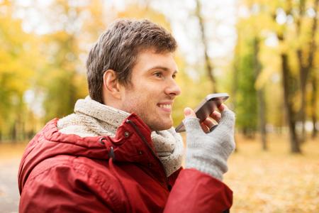 orador: el ocio, la tecnología, la comunicación y el concepto de la gente - la sonrisa del hombre inconformista utilizando grabador comando de voz o llamando en el teléfono inteligente en el parque de otoño Foto de archivo