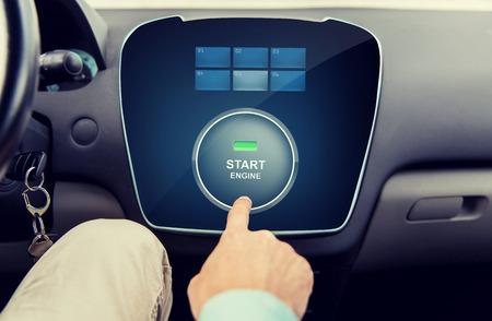 tecnología informatica: el transporte, la conducción, la tecnología y el concepto de la gente - cerca de la mano masculina usando la aplicación de arranque en el ordenador del coche Foto de archivo
