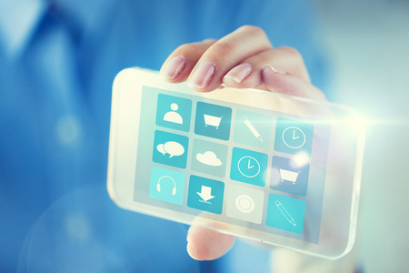 application icons: business, technology and people concept - close up of woman hand holding and showing transparent smartphone with application icons