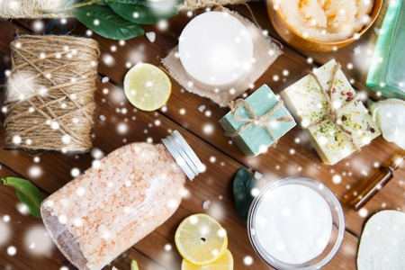 natural therapy: beauty, spa, therapy and wellness concept - natural body care cosmetics on wood over snow