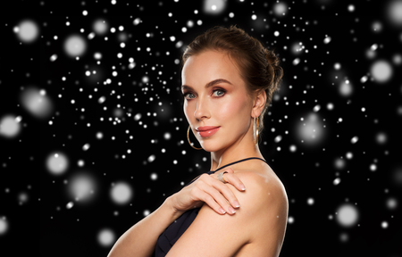 diamond background: people, luxury, jewelry, christmas and holidays concept - beautiful woman wearing diamond earring and ring over black background and snow