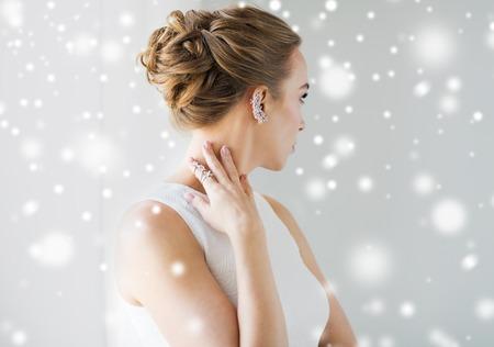 kerstmis, vakantie, juwelen, mensen en luxe concept - close-up van mooie vrouw met gouden ring en diamanten oorbel over grijze achtergrond en sneeuw