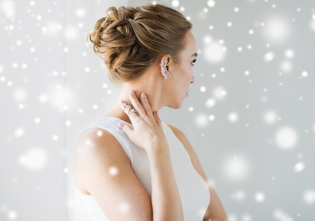 christmas, holidays, jewelry, people and luxury concept - close up of beautiful woman with golden ring and diamond earring over gray background and snow