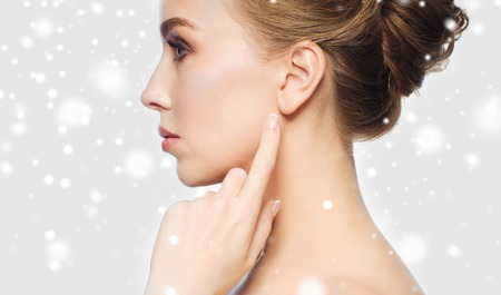 health, people, winter and beauty concept - close up of beautiful young woman pointing finger to her ear over gray background and snow