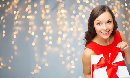 christmas, people, holidays and celebration concept - smiling woman in red dress with gift box over lights background Stock Photo