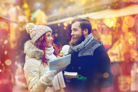 vestidos antiguos: holidays, winter, christmas, tourism and people concept - happy couple in warm clothes with map and city guide in old town