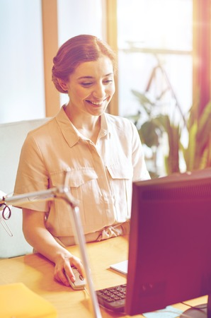 business, education, startup and people concept - happy woman or student with computer at office Stock Photo