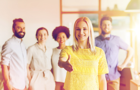 african american handshake: business, startup, people, gesture and teamwork concept - happy young woman greeting by handshake over creative team in office