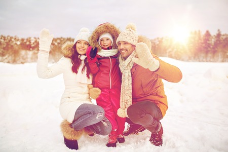 HI: parenthood, fashion, gesture, season and people concept - happy family with child in winter clothes waving hands outdoors Stock Photo