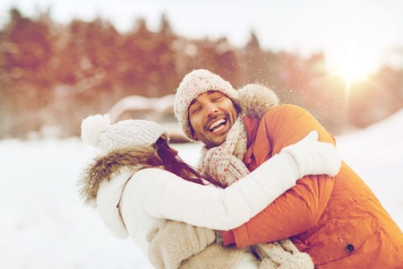 family outside: people, season, love and leisure concept - happy couple hugging and laughing outdoors in winter
