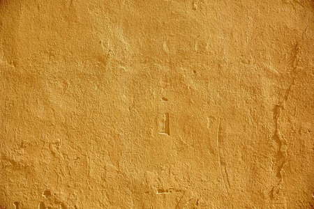 background and texture concept - yellow painted stone wall surface