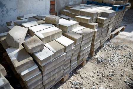 construction material: brickwork, construction and building material concept - bricks batch on wooden storage pallet