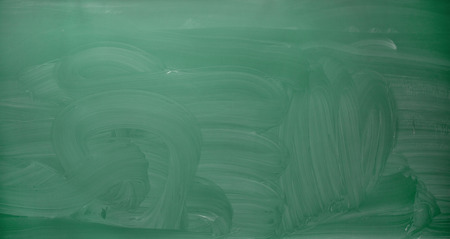 erased: school, education and learning concept - empty green chalkboard or blackboard with erased chalk traces