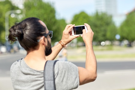 taking video: leisure, technology and people concept - hipster man taking picture or video by smartphone on street