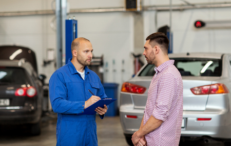 car maintenance: auto service, repair, maintenance and people concept - mechanic with clipboard talking to man or owner at car shop