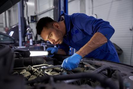 Service de voiture, la réparation, l'entretien et les gens concept - auto mécanicien homme avec lampe de travail à l'atelier Banque d'images - 65205655