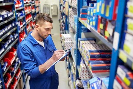 auto service, reparatie, onderhoud en mensen concept - automonteur man of smith schrijven naar het klembord op workshop of magazijn Stockfoto
