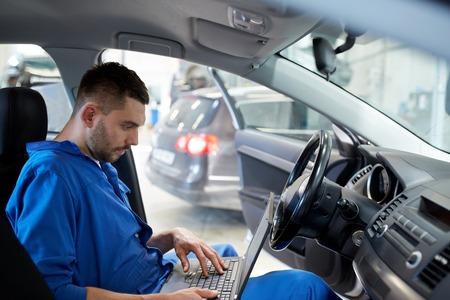 service de voiture, la réparation, l'entretien et les gens concept - homme mécanicien avec le système ordinateur portable de prise de diagnostic à l'atelier Banque d'images