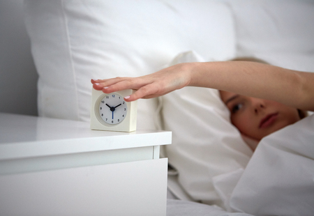 switching: rest, sleeping, time and people concept - close up of young woman switching off alarm clock in bed at home bedroom Stock Photo
