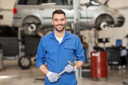Auto-Service, Reparatur, Wartung und Menschen Konzept - Automechaniker Mann oder Schmied mit dem Schraubenschlüssel an der Werkstatt Standard-Bild - 65205804