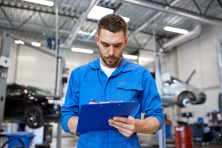 car service, repair, maintenance and people concept - auto mechanic man or smith with clipboard writing at workshop