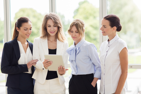 corporate women: people, technology, work and corporate concept - business team of women with tablet pc computer at office Stock Photo