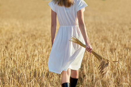 spica: happiness, nature, summer holidays, vacation and people concept - close up of young woman with cereal spikelets walking on field Stock Photo