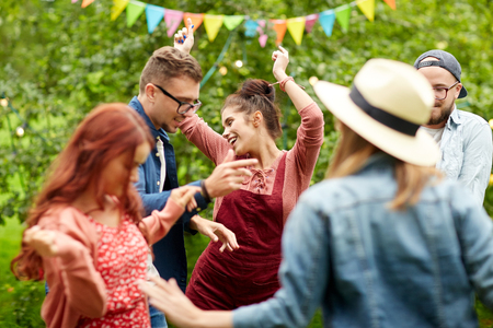 dances: leisure, holidays, fun and people concept - happy friends dancing at summer party in garden